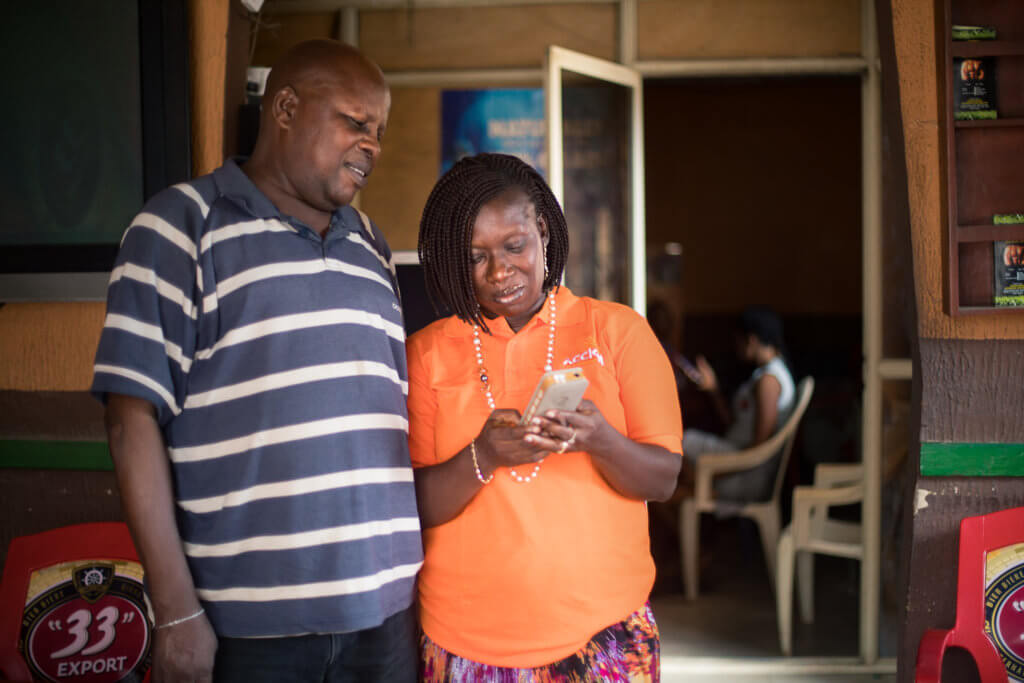 An Accion Microfinance Bank agent uses a tablet to support client Chief Akintunde