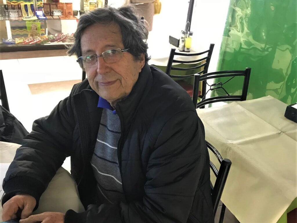 Jaime sits at a table at his restaurant