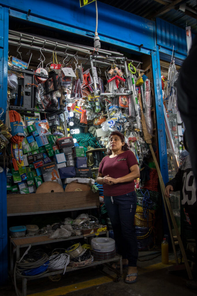 Flicitas stands in front of an array of hardware store merchandise