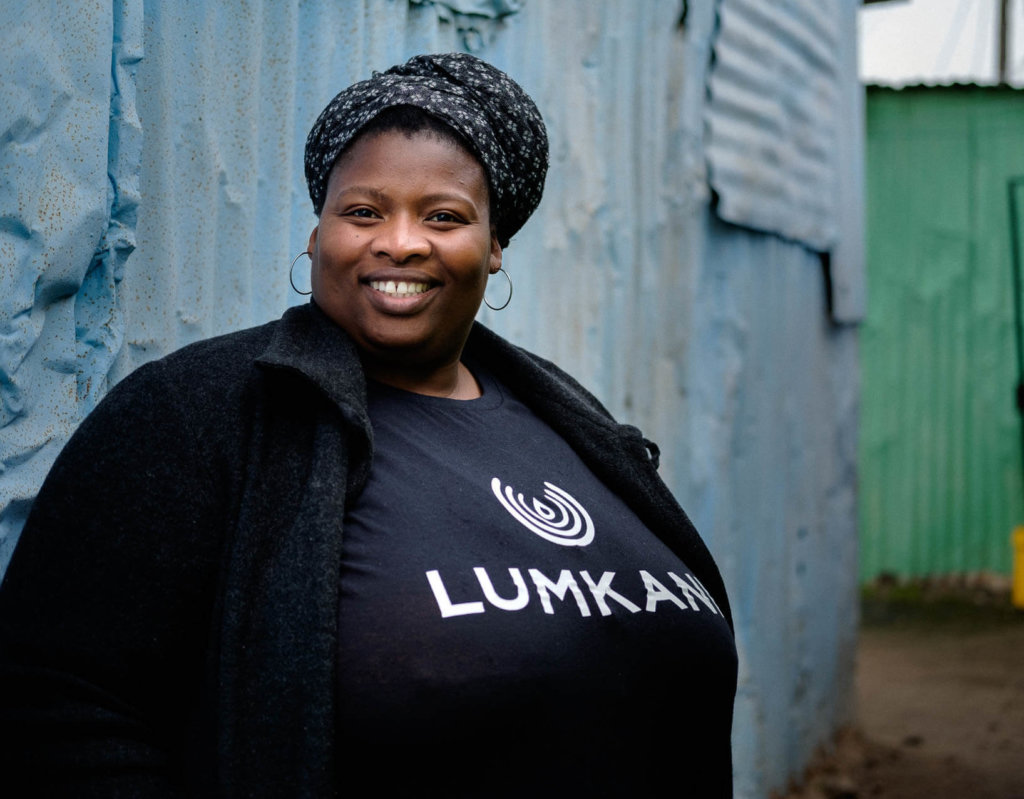 Zoliswa, an agent for Lumkani, in front of an informal settlement in South Africa