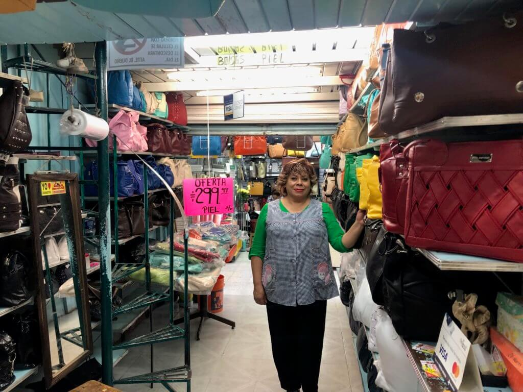 Ms. Bertha standing in front of her handmade leather bags in Mercado de Granaditas