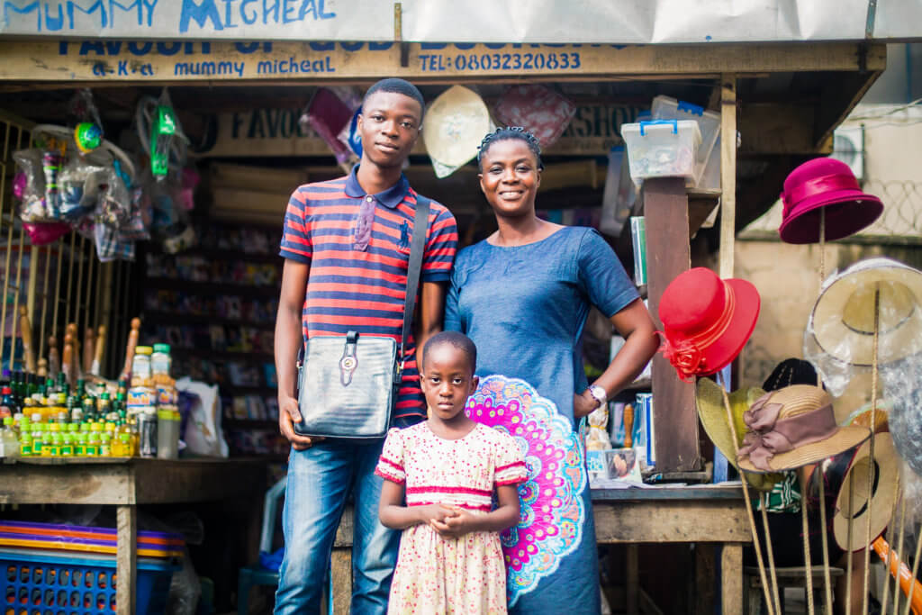 Ayodele Magret O with two of her children at her store