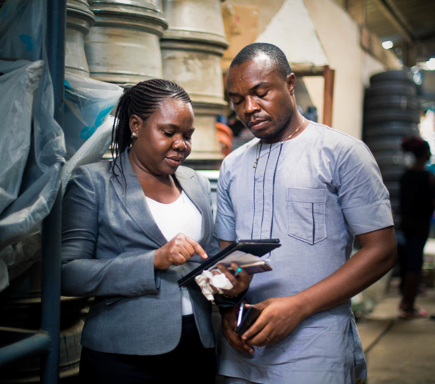 Accion Microfinance Bank loan officer uses a tablet to serve client Ezeh at his workshop