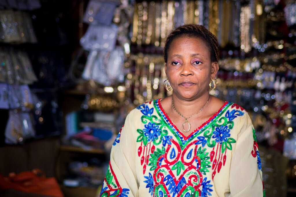 Yusuf Omolara sits in front of the jewelry she sells