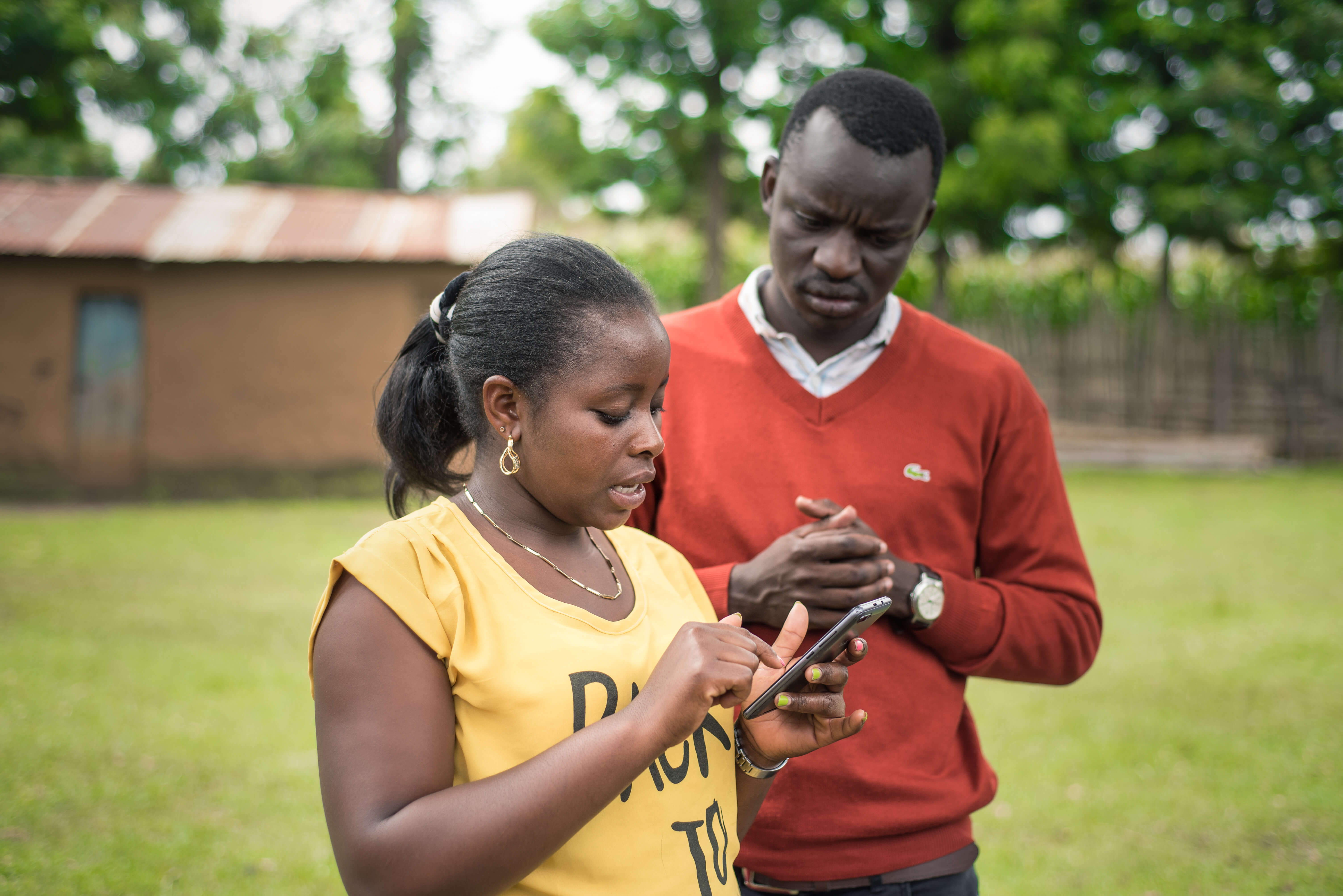 Apollo Agriculture field associate Rebecca setting up an account with a farmer client